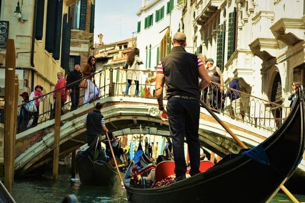 Photo de Venise: les gondoles à touche touche sur le canal et les touristes sur le pont qui les regardent passer